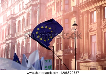 London, UK – October 20 2018: A European Union flag is waved above the crowd on Piccadilly, during an anti-Brexit march through central London, with the air turned pink from flares #1208570587