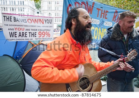 LONDON, UK -OCTOBER 31: Protesters playing guitar and singing with banners and slogans in the background on October 31, 2011 in London. - stock photo