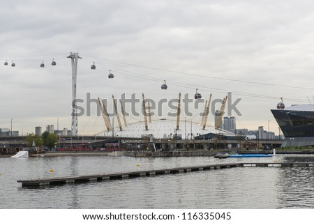 LONDON, UK - OCTOBER 20: Side view of Emirates Air Line cable car with O2 Centre, formerly Millennium Dome, in the background. October 20, 2012 in London.