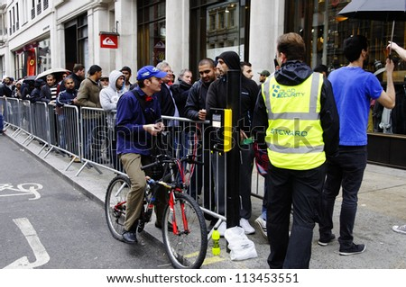 LONDON, UK - SEPTEMBER 21: People queuing in Hanover Street to buy the new iPhone 5 on September 21, 2012 in London. The iPhone 5 went on sale at the Apple Store on Regent Street. - stock photo