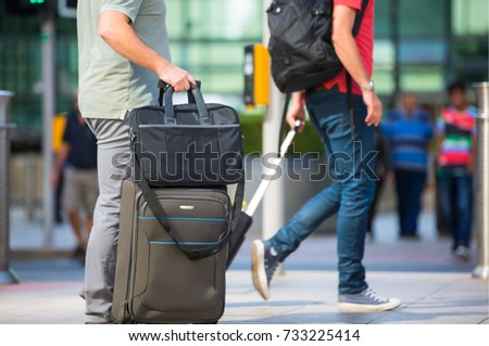 London, UK - 8 September, 2016: People with travel bags walking on the Canary Wharf square, business and financial aria. Modern life concept