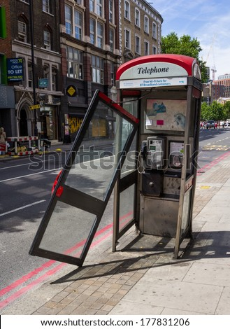 LONDON, UK - 15TH JULY 2013: A damaged public telephone box in London with the door hanging off