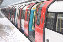 London underground train in the snow waiting for people to board