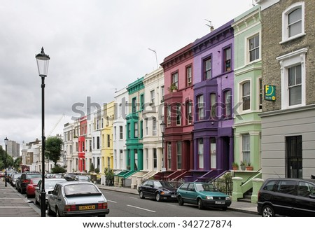 LONDON, UNITED KINGDOM - AUGUST 02: Colorful houses residential street with parked cars in Westminster London, UK - August 02, 2008; Cloudy London street with residential houses and parked cars.