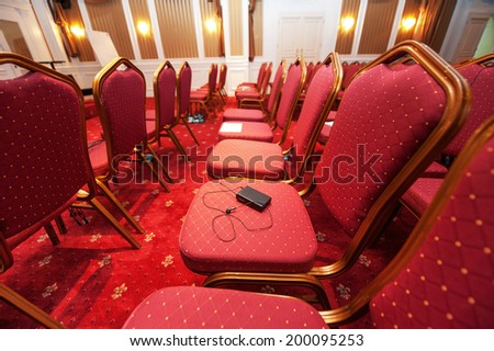 LONDON, UNITED KINGDOM - MARCH 31, 2012: Multy Language headphones used as a simultaneous translation equipment (interpretation equipment) lay on patterned chairs in empty luxury hotel conference hall