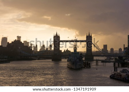 London/ United Kingdom - 10.03.2019: Silhouette picture of Tower Bridge and HMS Belfast with beautiful sunrise and buildings in the background