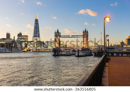 London view at sunset with Tower Bridge and modern buildings on background. There are some clouds on the blue sky and lights are turned on on streets and buildings. Travel and architecture concepts