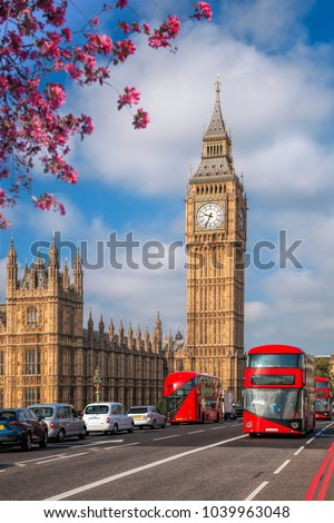 London with red buses against Big Ben during spring time in England, UK #1039963048