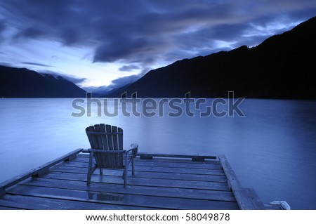 Lone adirondack chairs on a deck  at sunset