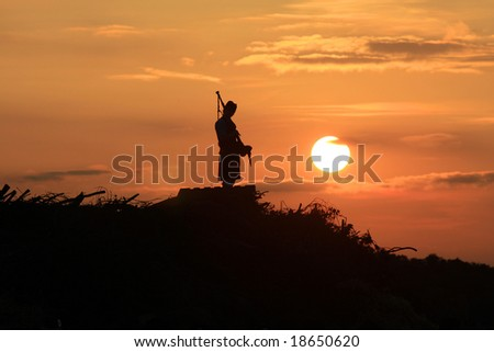 Lone bagpiper at sunset playing a sad tune
