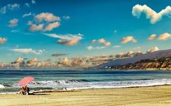 Lone beach goer under striped umbrella enjoys the beautiful California coast.