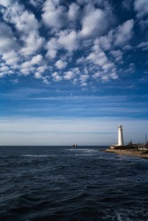 Lone beacon guards the ships. The lighthouse shows the way for boats. Wrecked ship lays nearby