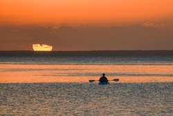 lone canoeist sitting out to sea watching the setting sun at Benguerra Island off the Mozambique coast