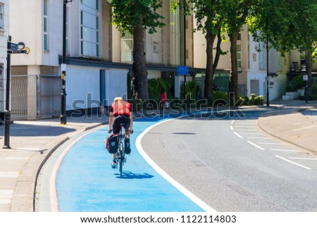 Lone Cyclist Cycles Along a Cycle Superhighway on the Victoria Embankment, London Stock photo ©