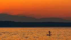 Lone female paddle boarder on Puget Sound during a beautiful orange smoky sunset