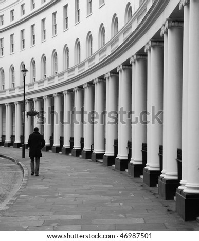 Lone figure walking along London's Park Crescent