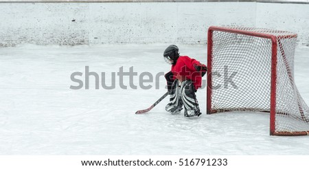 Lone goalie waits in anticipation as the offence gets closer to his net.  Hockey season, kids play the national game at a winter carnival.