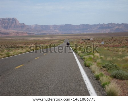 Lone highway in a remote area of Utah with two bicyclists peddling up the road. Red mesas on the horizon of the high desert. #1481886773