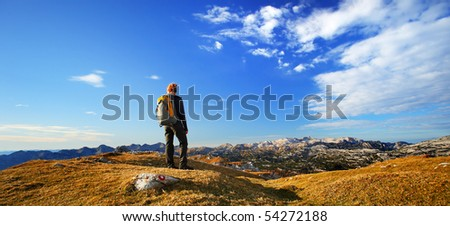 Lone hiker enjoying the view over the mountain summits in the Alps