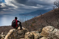 lone hiker resting in the mountains gazing at the seashore