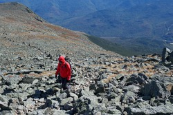 Lone hiker trekking to the summit of Mount Washington over a rocky terrain in cold windy weather