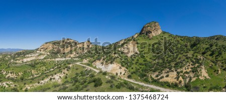 Lone hiking path winds beneath the hills of a grass covered hillside in southern California. #1375468724