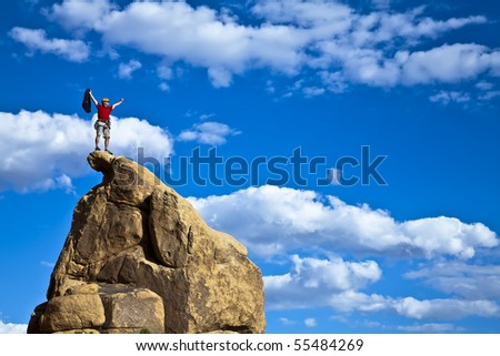 Lone, male climber celebrates on the summit of a rock spire.