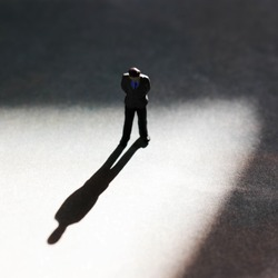 Lone man in empty space with dramatic shadow. Looking down at feet, he has a look of guilt or shame. Businessman guilty of white collar crime. Social isolation or social distancing. Isolated person.