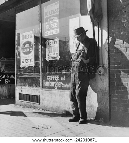 Lone man in farmer's overalls, San Francisco's Skid Row at Howard Street. Ruined farmers from Midwest added to homeless and unemployed populations in California. February 1936 photo by Dorothea Lange.