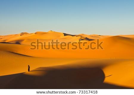 Lone man in the sand dunes at sunrise - Murzuq Desert, Sahara, Libya - stock photo