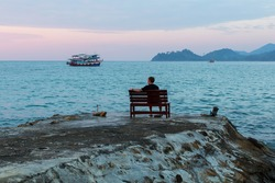 Lone man sitting on a bench at the evening sea coast.