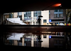 Lone man walking through flooded underpass with umbrella commuting to work in city centre flood water reflected rainy day mirrored silhouette bad severe weather big puddle Birmingham Mailbox