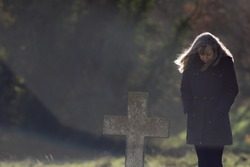Lone Mourner graveside. Mourning widow dressed in black with head bowed in cemetery. Middle-aged grieving person dressed in black standing by grave. Since woman paying respects to the dead. copy space