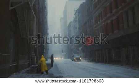 Lone person walking down snowy street in New York City