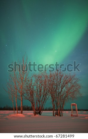 Lone phone booth stands in an open snow covered field under the northern lights.