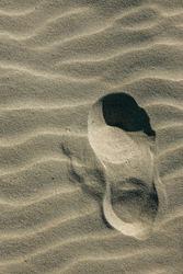 Lone single footprint crossing rippled sand, deep shadow.
