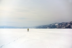 Lone stranger walking his path in the middle of snow white nowhere with distant mountains in background