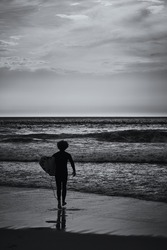 Lone surfer walks into the ocean to catch a wave. View on an Atlantic coast and dramatic cloudy sky at sunset. Concept of outdoor activities. Lisbon, Portugal.High Contrast. B&W color.