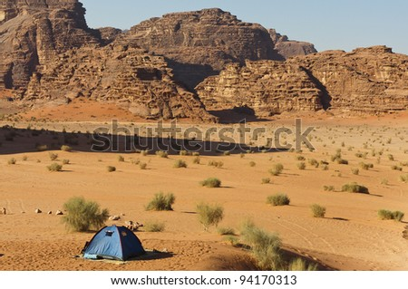 Lone tent in the Wadi Rum UNESCO World Heritage desert area. Long shadow from a towering peak.