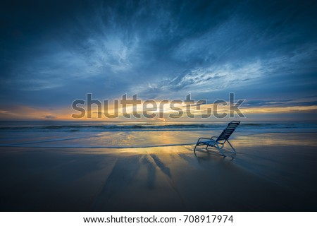 Lone vacation beach lounge chair at surf edge with dramatic high contrast orange sunrise ocean scene against deep blue cloud filled sky