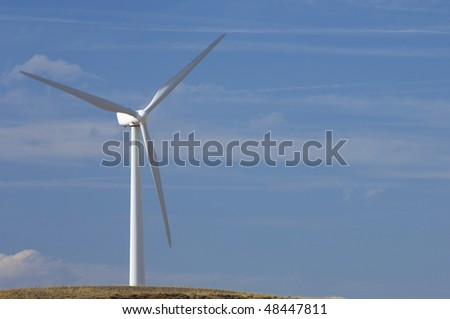 lone windmill with blue sky and clouds