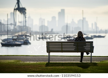 Lone woman in silhouette sitting on a bench by the waters edge with boats and city skyline in the background.