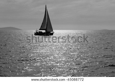 Lone yacht sailing in the Adriatic sea. Black and white image