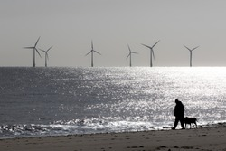 Loneliness and solitude. Peaceful landscape image of lonely person walking a dog. Mans best friend. Wind farm turbines on the sea beach horizon. Mindfulness and contemplation with tranquil background