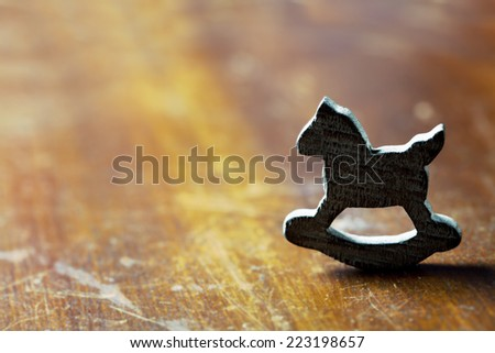 Loneliness concept: wooden rocking horse on wooden background