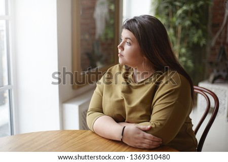 Loneliness concept. Young brunette plus size woman with black hair sitting at cafe table, feeling lonely, spending time alone, waiting for her lunch, looking through window with sad pensive expression