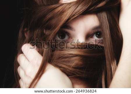 Loneliness stress anxiety and women concept. Closeup portrait beautiful woman dark haired, teen girl covering face by long brown hairs on black