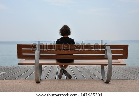 Loneliness teenager sitting on a bench at the sea shore  #147685301