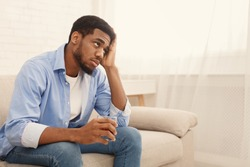 Loneliness. Young african american guy drinking alcohol at home alone, thinking about problems with glass of whiskey, free space