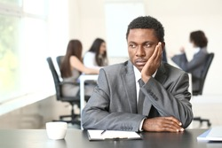 Lonely African-American businessman in office. Stop racism